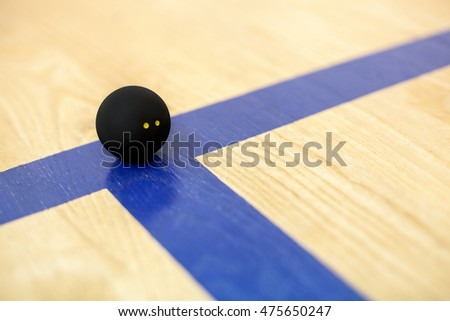 Black tennis ball with two yellow dots is lying on wooden court background - sport, fitness, healthy lifestyle and objects concept