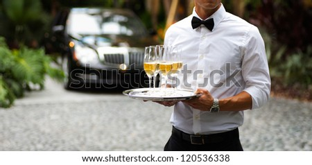 Black tie waiter serving champagne outdoors. - stock photo
