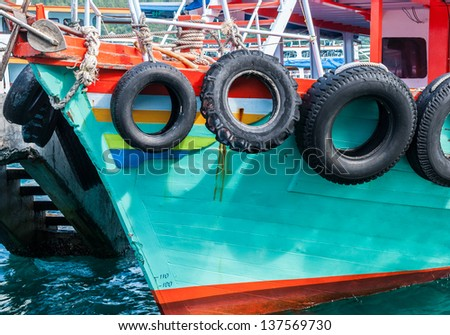 Black tire is hanging around the side boat for cushioning. - stock photo