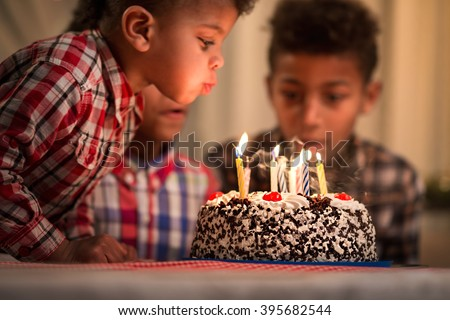 Black toddler blowing candles out. Child blows birthday candles out. Youngest brother's birthday. Spending festive time together. - stock photo