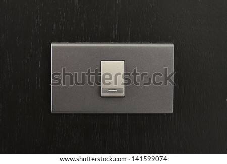 Black toggle switch on black surface - stock photo