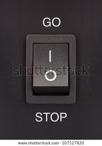 Black toggle switch on black surface - Go Stop - stock photo