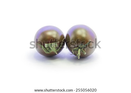 Black tomato couple with green stick on white background