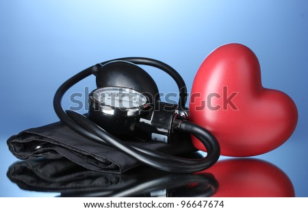 Black tonometer and heart on blue background - stock photo