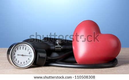 Black tonometer and heart on wooden table on blue background - stock photo