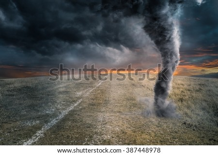 Black tornado funnel over field during thunderstorm - stock photo