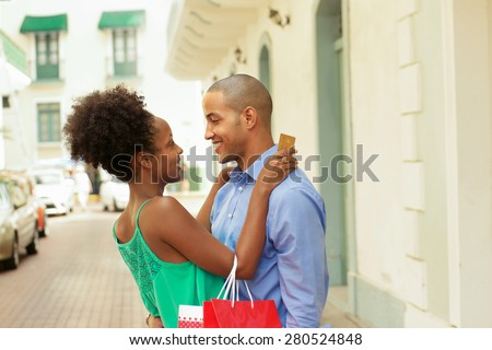 Black tourist heterosexual couple in Casco Antiguo - Panama City with shopping bags. The girl hold a credit card and looks at her boyfriend - stock photo