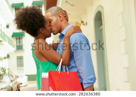 Black tourist heterosexual couple in Casco Antiguo - Panama City with shopping bags. The girl hold a credit card and kisses her boyfriend - stock photo