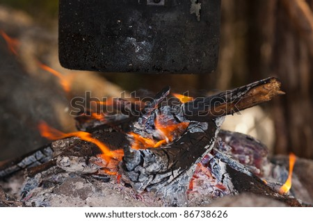 black tourist kettle on fire in wood close up