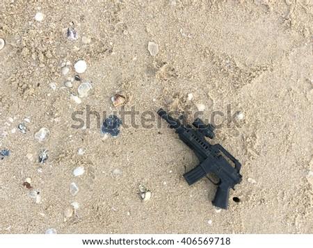 Black toy gun on the beach  - stock photo