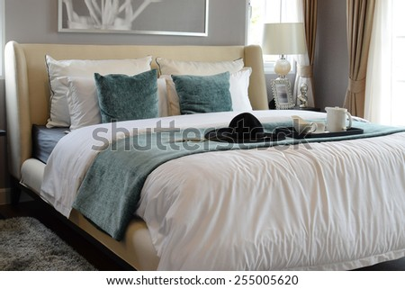 black tray of tea set with white and green pillows in classic style bedroom - stock photo