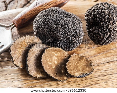 Black truffles on the old wooden table. - stock photo
