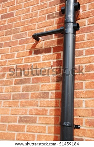 black tube on a brick house wall (used to drain water) - stock photo