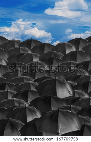 black umbrellas background with gloomy sky - stock photo