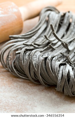 black uncooked noodles with squid sepia ink - stock photo
