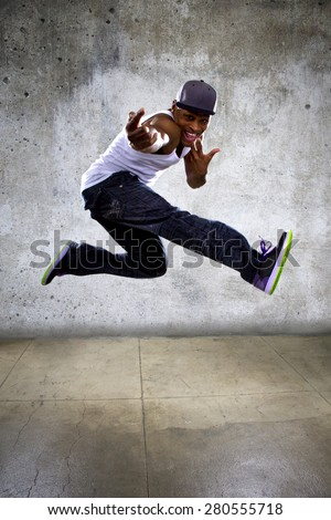 Black urban hip hop dancer jumping high on a concrete background.  The man is doing parkour or leaping. - stock photo