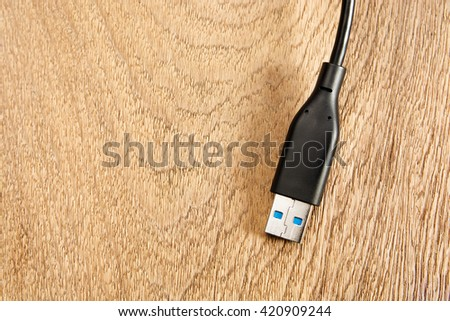 Black USB  connector on a wood background - stock photo