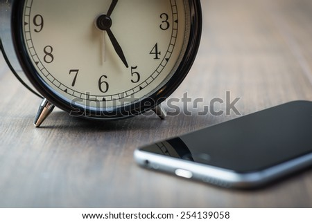 Black vintage alarm clock with phone on a wooden floor - stock photo