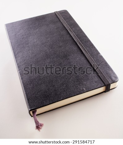 Black vintage notebook over white background, vertical image
