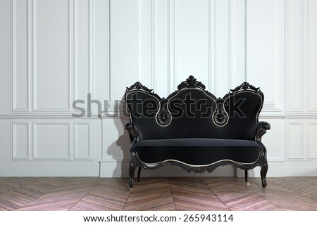 Black vintage ornately carved wooden couch against a white paneled wall on a bare parquet floor with herringbone pattern in a class house interior. 3d Rendering - stock photo