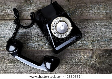 Black vintage phone on wooden background close-up, top view, pick up the phone - stock photo