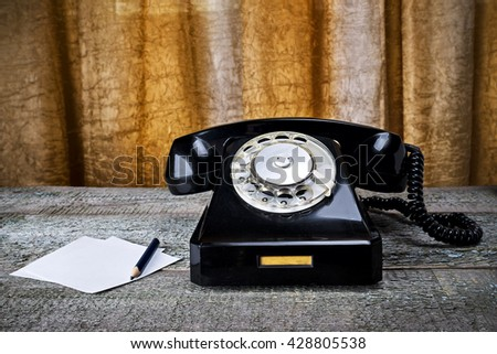 Black vintage phone on wooden background with pencil close-up, pick up the phone - stock photo
