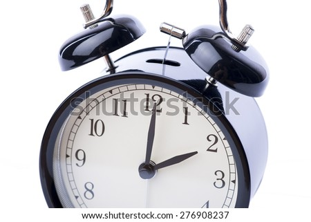Black vintage style alarm clock over the white background, isolated