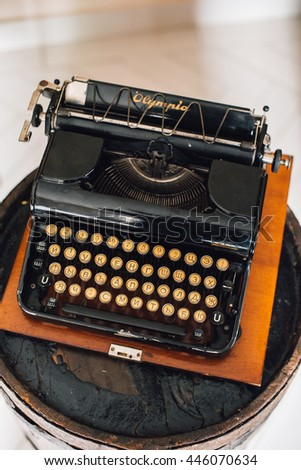Black vintage typewriter standing on barrel with cogs and gears on background. Wedding decorations.