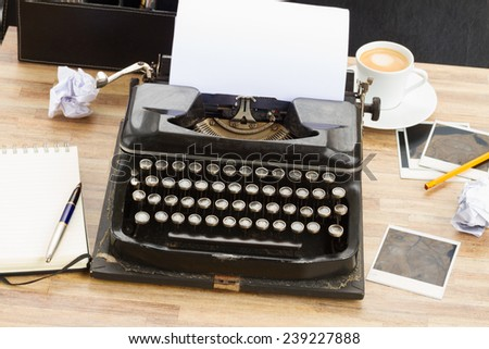 black vintage typewriter with blank  white page on working table - stock photo