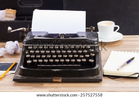 black vintage typewriter with empty white page on table - stock photo