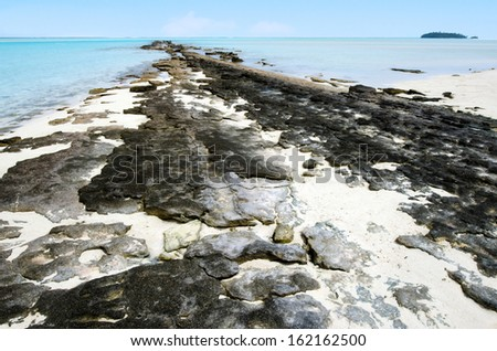 Black volcanic line of rock on One foot Island in Aitutaki Lagoon Cook Islands. - stock photo