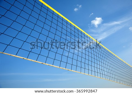 Black volleyball net is stretch from corner to corner against deep blue sky