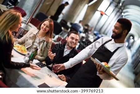 Black waiter serving terrace restaurant guests at table.Focus on the man