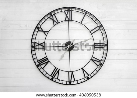 Black wall clock on white wooden background - stock photo