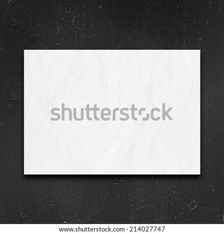 black wall with cracks and crumpled blank list of paper