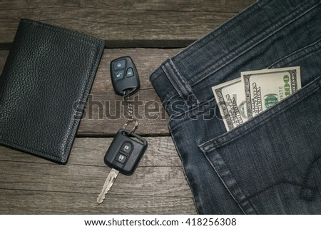Black wallet, car key and  american dollar in jeans on wooden board. - stock photo