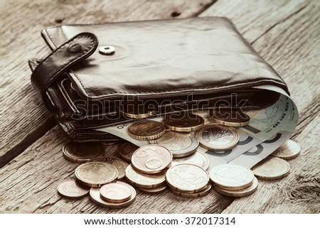 Black wallet with euro currency on the wooden background - stock photo