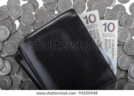 Black wallet with ten polish zloty paper money laying on one polish zloty coins. Money and savings concept. - stock photo