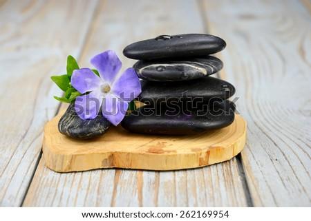 Black warmth zen stones for health piles up on old knotted wooden background with  decoration