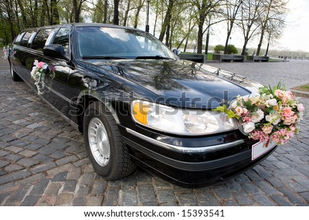 Black Wedding Limousine. Ornated with flowers.