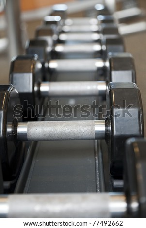 Black weights on a rack in a gym