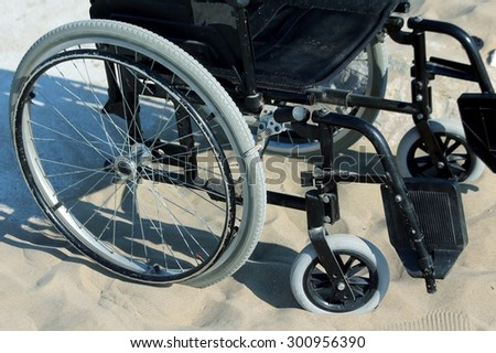 black wheelchair stuck in the sand on the seashore