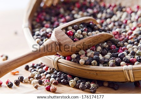 black ,white and red peppercorns on wooden table