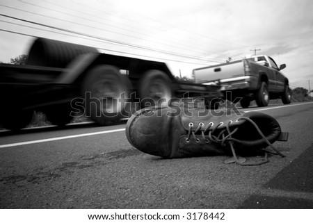 black & white conceptual photograph of a lost boot - stock photo