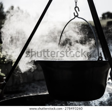 Black White cooking pot over campfire - stock photo