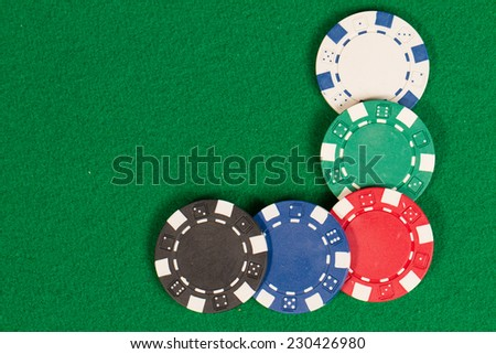 Black, White, Green, Blue and Red Playing Poker Chips in a green background