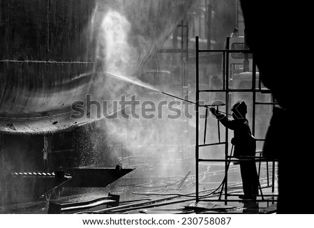 Black & white image of a dock worker steam cleaning a ships hull