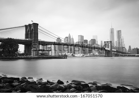 Black & White long exposure shot of the Brooklyn Bridge and New York skyline across the East River on a cloudy summer morning. - stock photo
