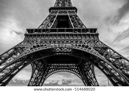 Black-white photo of close-up element part of Eiffel tower in Paris against dramatic twilight sky at evening summer time.