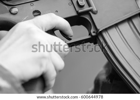 Black & white photo of soldier pulling the trigger on assault rifle.Military firearms & ammunition.Focus on soldiers finger on trigger.National guard warrior man protecting the peace.Special forces